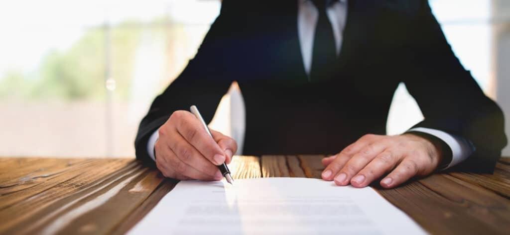 Osoba w garniturze podpisująca dokument