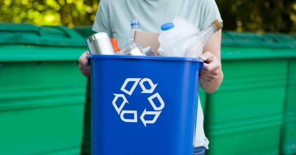 Osoba trzymająca kosz na śmieci z znakiem recyklingu