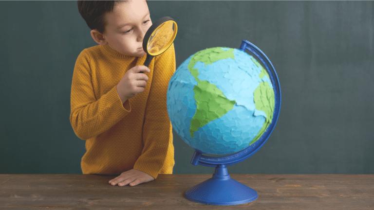 dziecko ogląda globus przez lupę